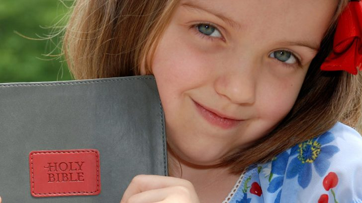 girl holding bible for first and second grade bible curriculum page
